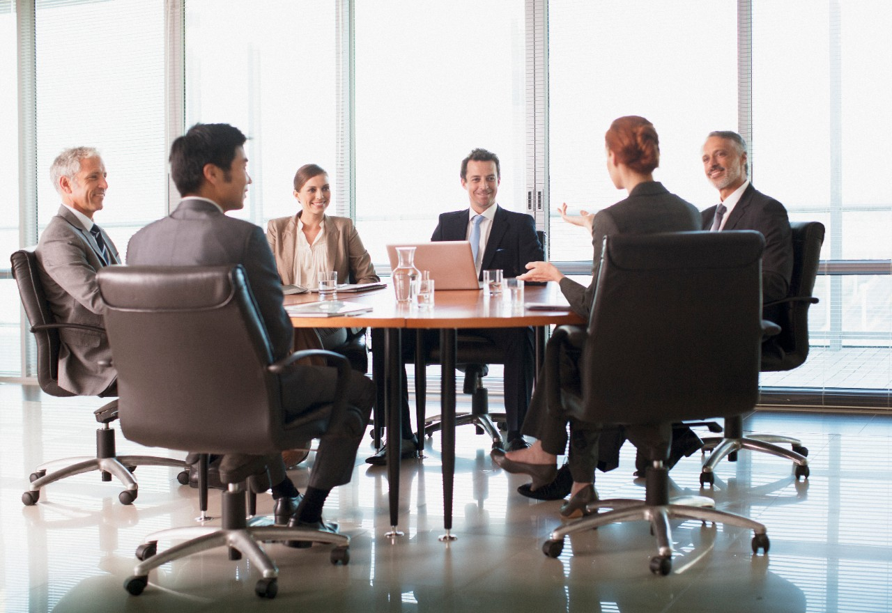 Businesspeople meeting at table in conference room, office, group